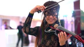 Красивая маленькая девочка играя на электрической скрипке на красивом концертном зале видеоматериал