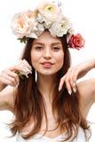 Красивая маленькая девочка усмехаясь и представляя с цветками на белой предпосылке стоковая фотография