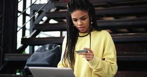 Красивая молодая африканская женщина используя кредитную карточку для того чтобы сделать сделку из тетради в современной зале офи видеоматериал