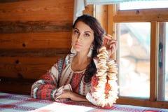 Красивая молодая женщина в национальном костюме сидя в хижине стоковые фотографии rf