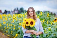 Красивая молодая женщина на поле солнцецвета с букетом цветет Счастливая девушка на день захода солнца лета стоковая фотография rf