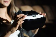 Красивая молодая женщина нося виртуальный шлемофон Усмехаясь битник используя стекла VR стоковое фото