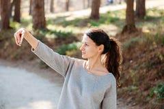 Красивая молодая женщина принимая фото с мобильным телефоном self Vlog Видео- звонок стоковые фотографии rf