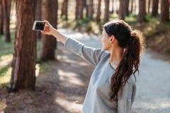 Красивая молодая женщина принимая фото с мобильным телефоном self Vlog Видео- звонок стоковое фото rf