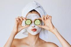 Красивая молодая женщина с лицевой маской на ее стороне держа куски огурца Забота кожи и обработка, спа, естественная красота и стоковое изображение