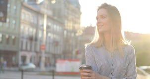 Красивая молодая дама sipping ее кофе утра на улице и усмехается на камере Портрет Конца-вверх видеоматериал