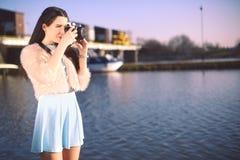 Красивая девушка на пристани около реки Модель в голубом платье с длинными волосами Девушка на горячем солнечном дне фотографируя стоковое изображение