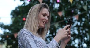 Красивая девушка печатает по ее телефону и усмехается joyfully outdoors Взгляд со стороны, портрет конца-вверх акции видеоматериалы