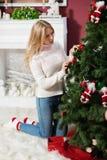 красивая девушка  сидит около рождественской елки Royalty Free Stock Photo