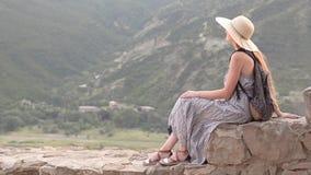 Красивая девушка с рюкзаком и шляпой сидя и восхищая взгляд гор холм акции видеоматериалы