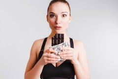 Красивая девушка фитнеса на светлом - серая предпосылка с шоколадом Концепция общаться с желанием съесть старье стоковое фото