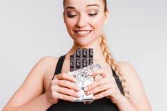 Красивая девушка фитнеса на светлом - серая предпосылка с шоколадом Концепция общаться с желанием съесть старье стоковая фотография