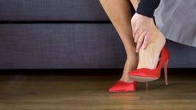 Красивая сексуальная бизнес-леди принимает красные высокие пятки и массажи тягостные ноги видеоматериал
