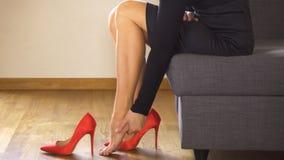 Красивая сексуальная бизнес-леди принимает красные высокие пятки и массажи тягостные ноги сток-видео