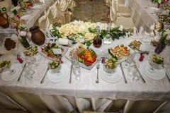 Красивая сервировка стола с посудой и цветками для партии, приема по случаю бракосочетания или другого праздничного события Стекл стоковые фото