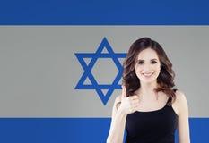 Красивая счастливая молодая женщина против предпосылки флага Израиля В реальном маштабе времени, образование и работа в Израиле стоковые фото