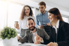 Красивые бизнесмены используют компьютеры и усмехаются пока работающ в офисе стоковая фотография rf