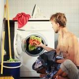 Красивые нагрузки человека в одеждах стиральной машины грязных Домашнее хозяйство холостяка, мужская концепция домохозяйки стоковое фото