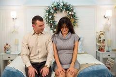 Красивые целуя беременные пары в любов на рождестве, имеющ остатки на рождестве праздники перед Новым Годом развилки стоковые фото