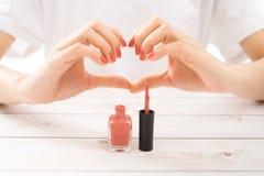 Красивые руки женщин улучшают красные ногти делая сердце стоковые изображения rf