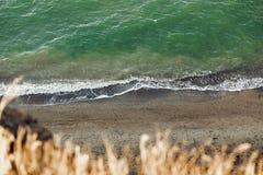 Красивый взгляд сверху голубых морской воды и волн от песочной скалы с травой Ландшафт скалы и океана пляжа каникула территории л стоковые фотографии rf