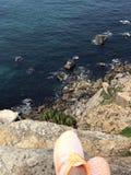 Красивый вид: море, утесы, камни на ноге девушки в оранжевых тапках стоковое фото