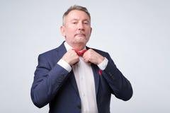 Красивый зрелый бизнесмен в официальном костюме регулирует его связь стоковая фотография
