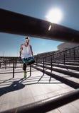 Красивый молодой мышечный человек в современной одежде спорта сидя после тренировки на шагах рядом со стадионом на яркое солнечно стоковое фото rf