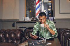Красивый молодой человек в парикмахерскае ждет мастера в зале ожидания пока выпивающ кофе стоковое изображение