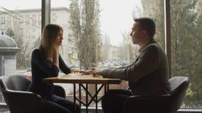 Красивый молодой человек с его женщиной имеет дату на ресторане акции видеоматериалы
