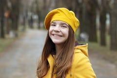 Красивый девочка-подросток в желтых пальто и берете стоковое изображение rf