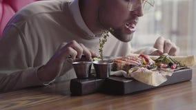 Красивый человек в стеклах есть его еду без использовать конец столового прибора вверх Клиент есть зажаренных рыб служил в кафе сток-видео