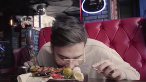 Красивый человек в стеклах есть его еду без использовать конец столового прибора вверх Удовлетворяемый клиент есть зажаренных рыб сток-видео