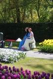 2 красивых молодых азиатских дамы одели традиционные костюмы сидят на banch весной приурочивают в цветочном саде Keukenhof стоковое изображение rf