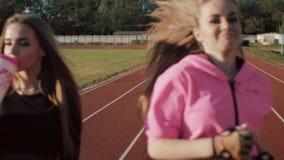 2 красивых молодых женщины фитнеса разрабатывая outdoors Девушки фитнеса на стадионе На переднем плане, напитки девушки акции видеоматериалы