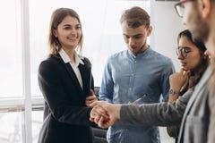 Красивое усмехаясь положение коммерсантки и handshaking бизнесмена в офисе, приятно познакомиться, первое впечатление, повышаемый стоковые фото