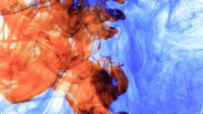 Красные и синие чернила которые входят в воду формируя оживленные текстуры, идеал отснятого видеоматериала для motiongraphic и co сток-видео
