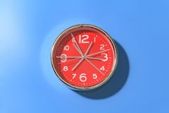 Красные круглые часы с большое количество рук с большими белыми номерами на зеленой предпосылке стоковое изображение
