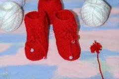 Красные связанные добычи младенца, красные и белые шарики пряжи шерстей для вязать и красного помпона пряжи на пинке - голубой пр стоковая фотография rf