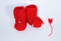 Красные связанные добычи младенца и красный помпон пряжи на белой предпосылке стоковое фото rf