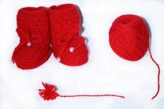 Красные связанные добычи младенца, красный шарик пряжи шерстей для вязать и красный помпон пряжи на белой предпосылке стоковое фото