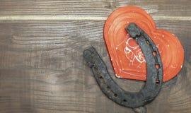 Красные сердце и подкова на деревянной доске стоковое фото
