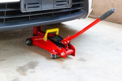 Красный инструмент поднимает автомобиль домкратом подъема для обслуживания проверки ремонта стоковое фото rf