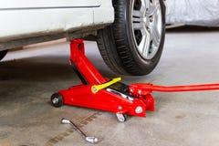 Красный инструмент поднимает автомобиль домкратом подъема для обслуживания проверки ремонта стоковое изображение