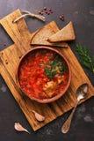 Красный суп с борщом говядины служил в плите глины с хлебом рож на разделочной доске, взглядом сверху Русская еда стоковое изображение