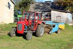 Красный трактор припаркованный рядом с домом семьи со старым аграрным оборудованием в предпосылке окруженной с амбаром и другой т стоковое изображение rf