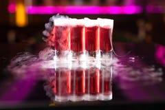 4 красных съемки коктейля с дымом на отражательной таблице зеркала стоковые фото