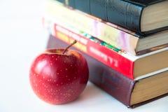 Красное зрелое сочное яблоко около книг иллюстрация штока