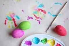 крася пасхальные яйца Краски в палитре, красочных яйцах и печати ладони ребенка на таблице, плоском положении стоковые изображения rf