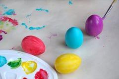 крася пасхальные яйца Палитра с красками, покрашенными яйцами и щеткой на таблице стоковые фотографии rf